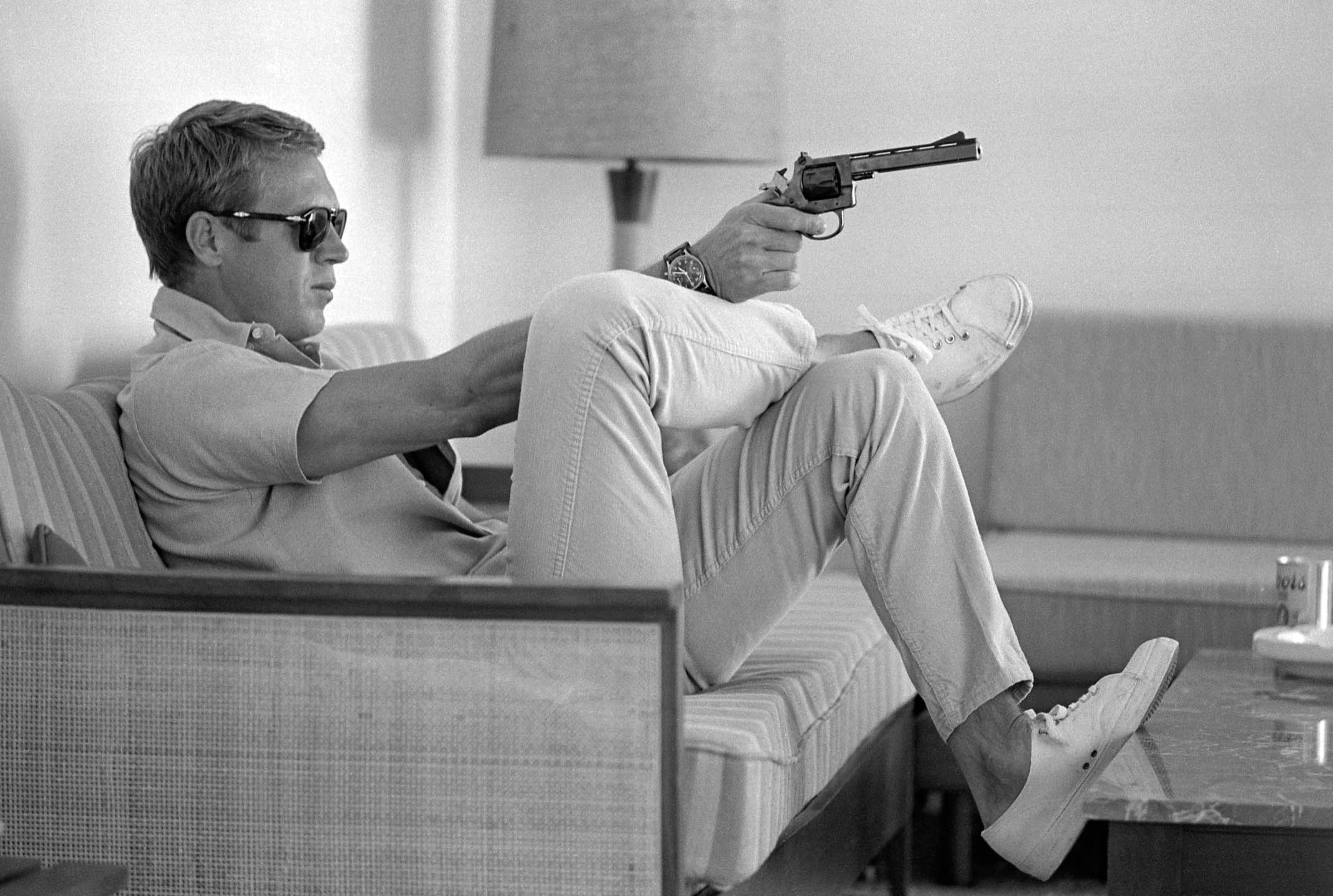 Steve McQueen aims a pistol in his living room.