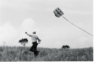 Portrait of photographer Henri Cartier-Bresson flying a kite in Provence.